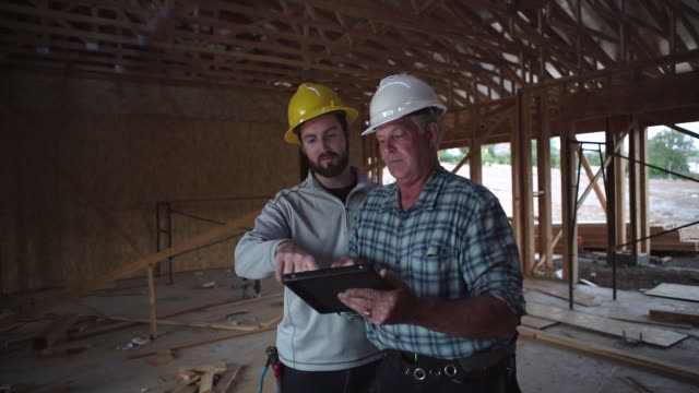 ms ts two men looking at plans on a digital tablet at a building site - contractor stock videos and b-roll footage