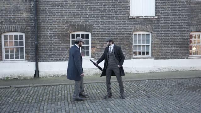 stockvideo's en b-roll-footage met twee mensen ontmoeten elkaar op een kasseienstraat die tweed kostuums en vlakke kappen draagt die een argument hebben - acteur