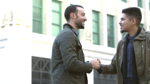 vídeos y material grabado en eventos de stock de dos hombres, reunión, saludo en la esquina de calle de la ciudad - two people