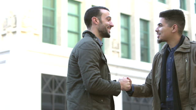 two men meeting, greeting on city street corner - greeting stock videos & royalty-free footage