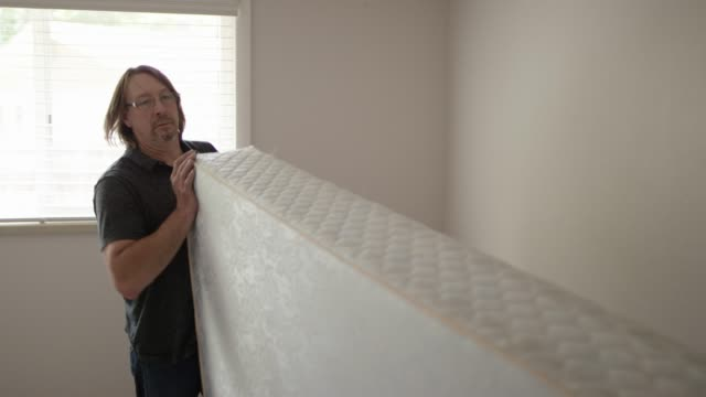 Two Men Move a Mattress out of a Bedroom