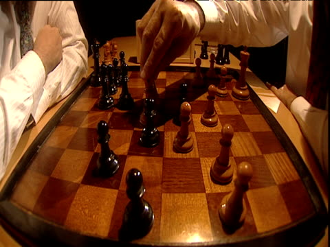 two men move pieces during closing stages of game of chess then shake hands to agree to stalemate - chess stock videos & royalty-free footage