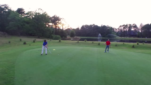 Two men on a putting green at sunset