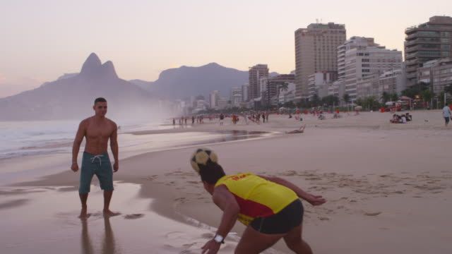 Two men on Ipanema beach playing soccer