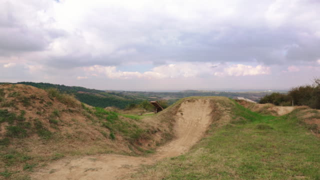 Two men on mountain bikes riding and jumping over small dirt hills.