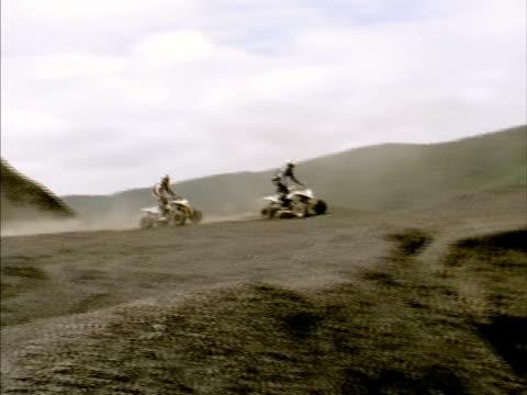 stockvideo's en b-roll-footage met ws, ts, two men on quad bike jumping on dirt racetrack, california, usa - hoofddeksel