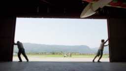 Two men opening the door of the hangar at the airport and revealing a sunny airport