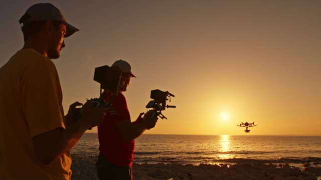 two men operating a drone on the beach at sunset - pilot stock videos and b-roll footage