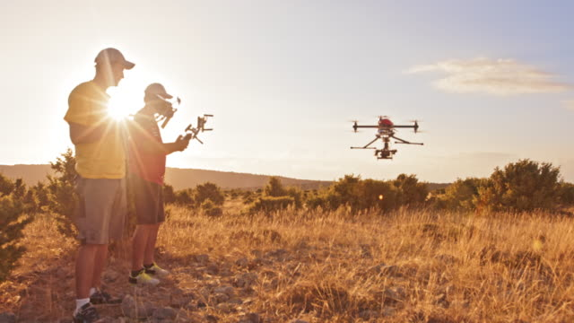 ds two men operating the drone on hilltop at sunset - wide stock videos & royalty-free footage