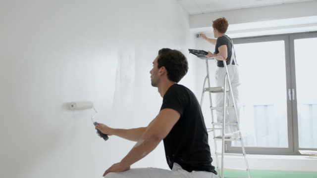 ms two men painting wall / london, england, united kingdom - bricolage video stock e b–roll