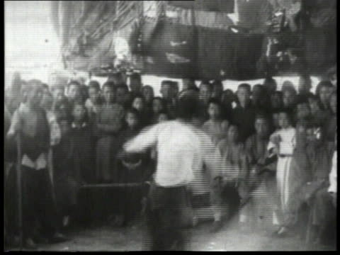 1932 ws two men participating in a sward fight while audience watches / china  - 1932 stock videos & royalty-free footage