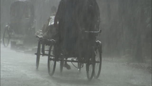 vídeos de stock e filmes b-roll de two men pedal rickshaws in a monsoon. available in hd. - monção