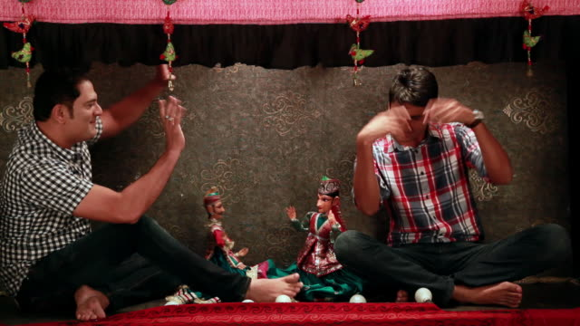 Two men performing with puppets in a puppet show, Delhi, India