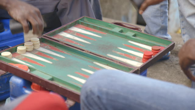 Two men play a game of backgammon outdoors.