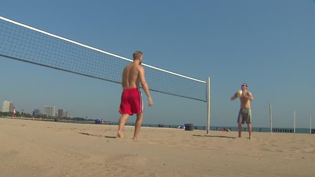 two men playing beach volleyball - ヒート点の映像素材/bロール