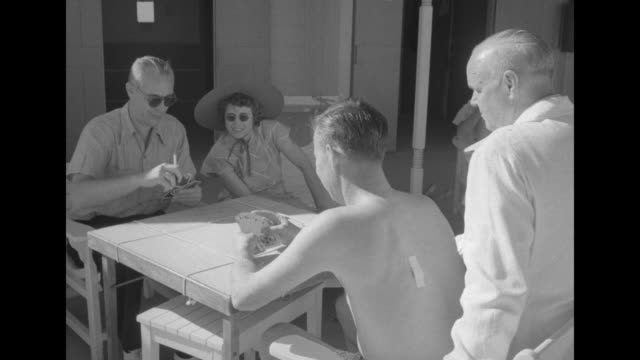 vs two men playing cards with a couple looking on man with bandage on back with couple wearing sunglasses group of women on chaise lounges at cabanas... - blus bildbanksvideor och videomaterial från bakom kulisserna