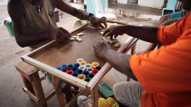 vídeos de stock, filmes e b-roll de ms two men playing dominoes together on table / salvador, bahia, brazil  - grupo mediano de animales