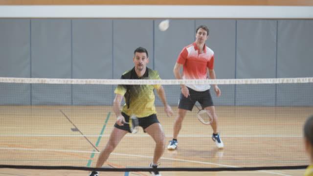 vídeos de stock, filmes e b-roll de dois homens jogando badminton indoor de duplas contra duas mulheres - badmínton esporte