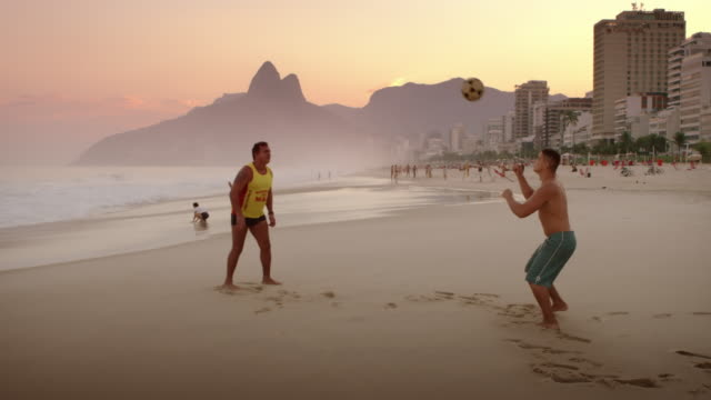 Two men playing football on Ipanema beach