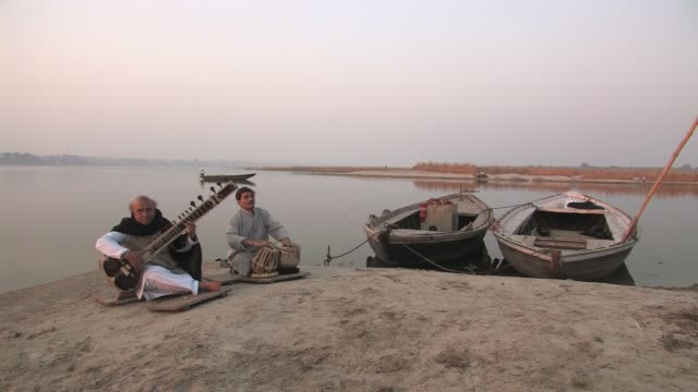 WS, Two men playing sitar and bongo drums on bank of Ganges River, Varanasi, Uttar Pradesh, India