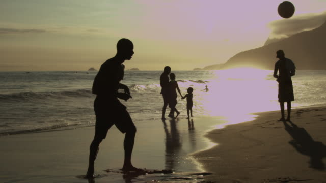 Two men playing soccer at Ipanema Beach on sunset
