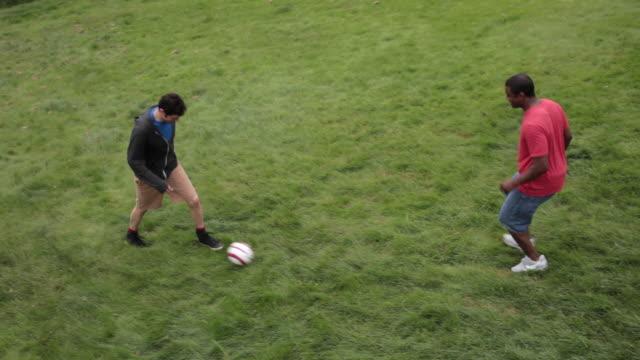 ms pan two men playing soccer on lawn / portland, oregon, united states - nur männer über 30 stock-videos und b-roll-filmmaterial