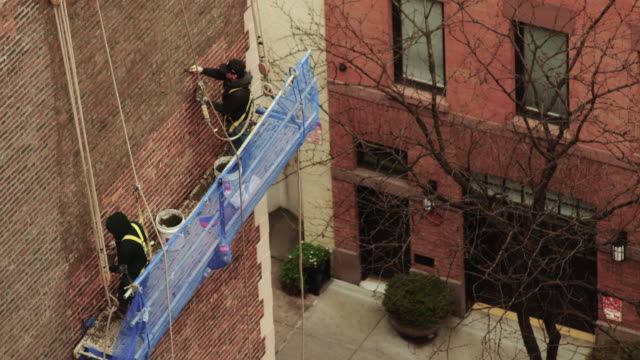 two men point bricks while suspended from scafolding in new york city. - 足場点の映像素材/bロール