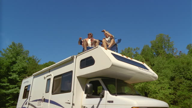 ms la two men pointing and sitting on deck chairs on roof of parked motor home / asheville, north carolina, usa - motor home stock videos and b-roll footage