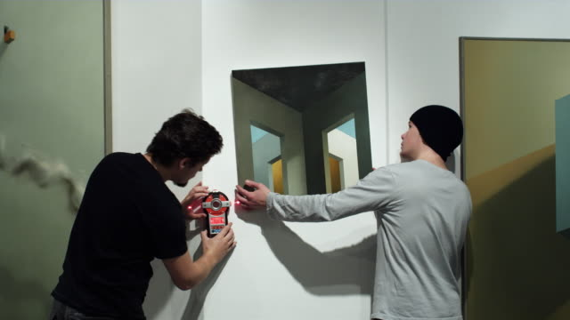 MS Two men positioning painting and drawing level in gallery space / Bilbao, Vizcaya, Spain.
