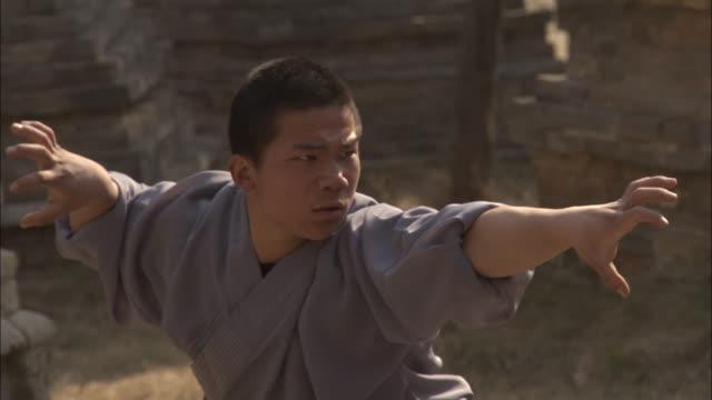 two men practice kung fu moves, beijing, china - カンフー点の映像素材/bロール