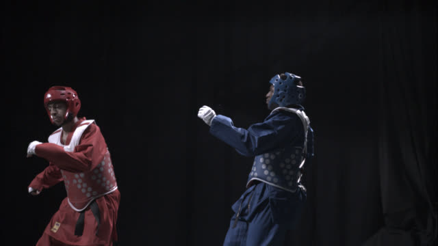 two men practice taekwondo in a studio. - taekwondo stock videos & royalty-free footage