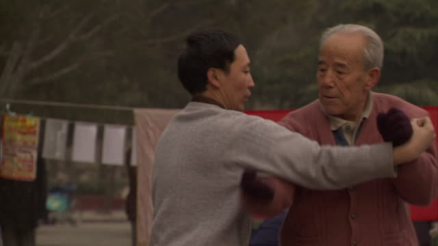 slo mo ms pan two men practicing martial arts in public park, beijing, china - martial arts stock videos & royalty-free footage