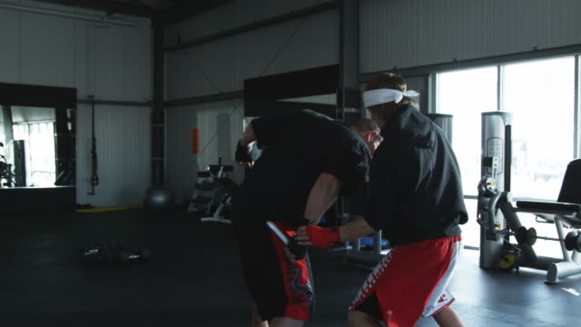 stockvideo's en b-roll-footage met two men practicing self-defense and martial arts in a gym - haarband