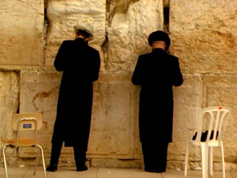 ms, two men praying facing wailing wall, jerusalem, israel - wailing wall stock videos & royalty-free footage