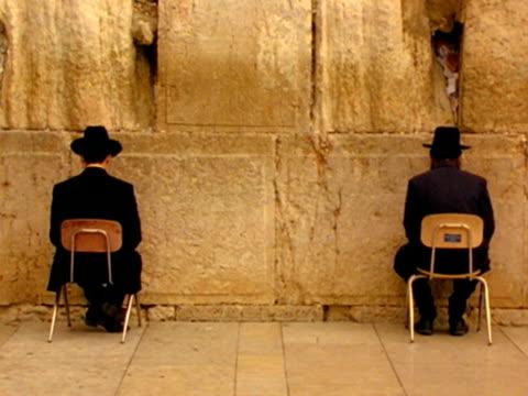 vídeos y material grabado en eventos de stock de ms, two men praying sitting on chairs facing wailing wall, jerusalem, israel - simetría