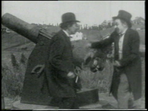 stockvideo's en b-roll-footage met b/w 1915 two men preparing to fire cannon on grassy hill / short - 1915