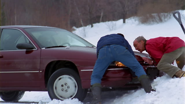 Two men push a car out of a snowbank.