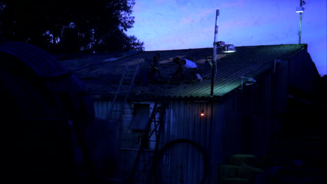two men reinforce an aluminum roof on a wood barn as a storm approaches. available in hd. - changing lightbulb stock videos & royalty-free footage