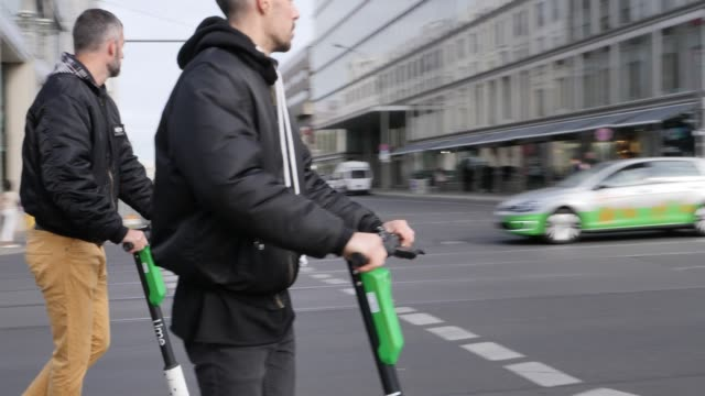 vídeos y material grabado en eventos de stock de two men ride electric scooters in the city center on september 20 2019 in berlin germany - scooter