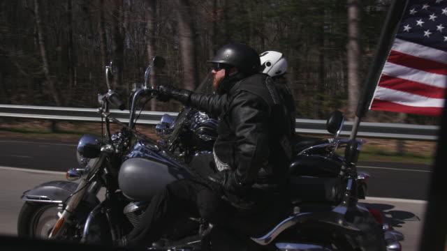 vídeos de stock e filmes b-roll de two men ride motorcycles on highway - bandeira