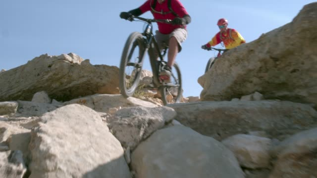 two men ride mountain bikes down rocks in the desert - trail ride stock videos and b-roll footage