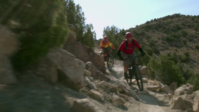 two men ride mountain bikes down rocks in the desert - andare in mountain bike video stock e b–roll