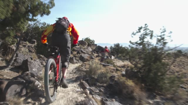 two men ride mountain bikes up rocks in the desert - trail ride stock videos and b-roll footage