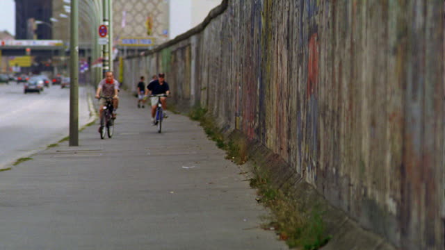 two men riding bicycles toward camera on sidewalk next to berlin wall / berlin, germany - omgivande mur bildbanksvideor och videomaterial från bakom kulisserna