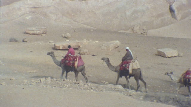 ha ws pan two men riding camels in desert with third camel following/ zo ws men on camels passing ruins/ egypt - history stock videos & royalty-free footage