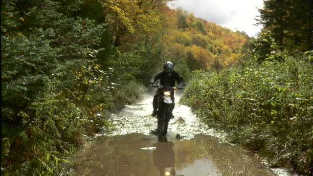 WS Two men riding dirt bikes through puddles on dirt path in forest / Stowe, Vermont, USA