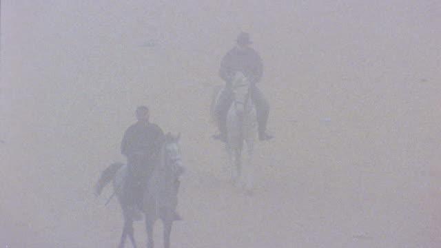 vidéos et rushes de ha ws two men riding horses through fog/ egypt - couvre chef