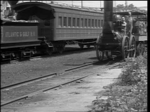B/W two men riding on early 1800s steam train past camera / newer train in background