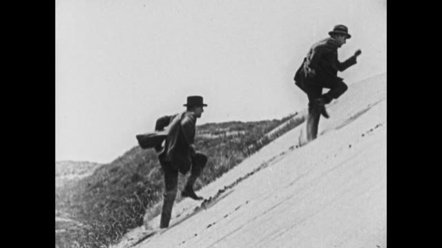 1924 two men run in place as they chase each other up sandy hill - silent film stock videos & royalty-free footage