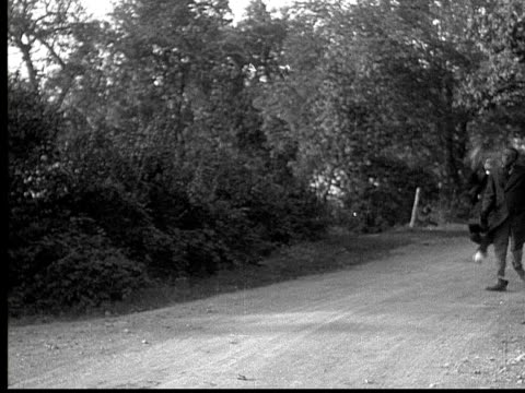 1916 b&w ws two men running down dirt road, one with a bandaged foot  - kompletter anzug stock-videos und b-roll-filmmaterial